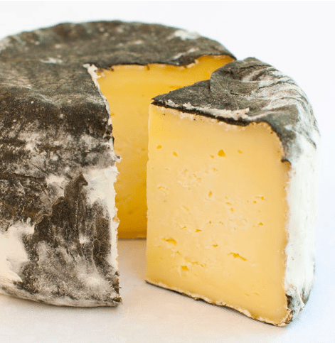 Round of St. Pat cheese with a thick slice cut out.