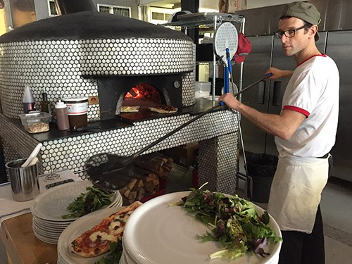 Owner Luca Arrigoni manning the pizza oven at Sottocasa.