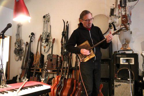 Ken Butler jamming on a shovel guitar in his studio. Photo: Megan Penmann